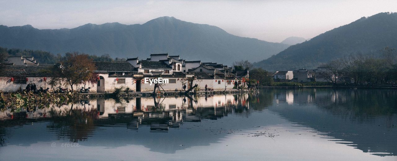 Panoramic View Of Houses By Lake Against Mountains