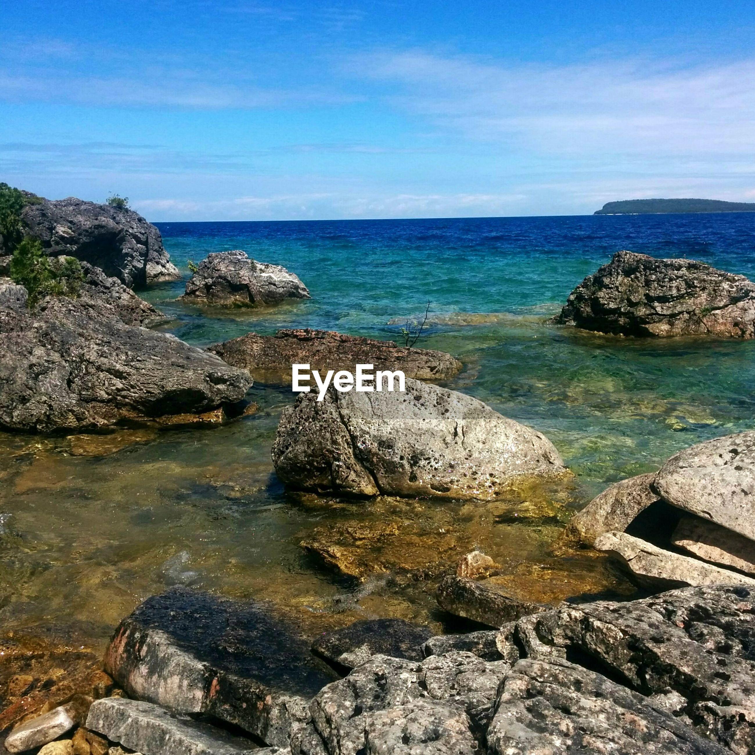 Rocks on sea against blue sky