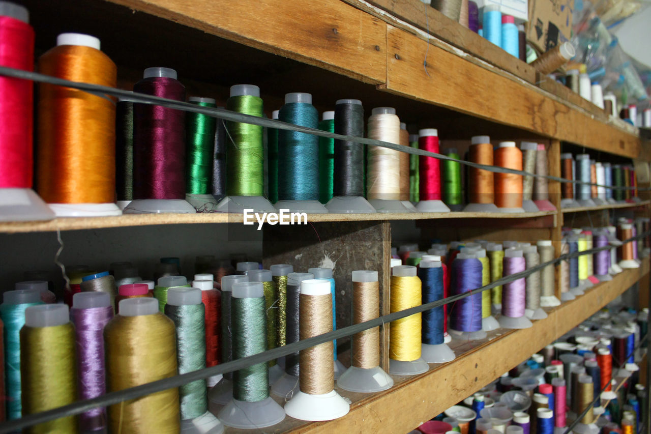 choice, multi colored, large group of objects, thread, shelf, variation, no people, indoors, still life, arrangement, spool, in a row, side by side, art and craft, textile, collection, industry, abundance, selective focus, close-up, order