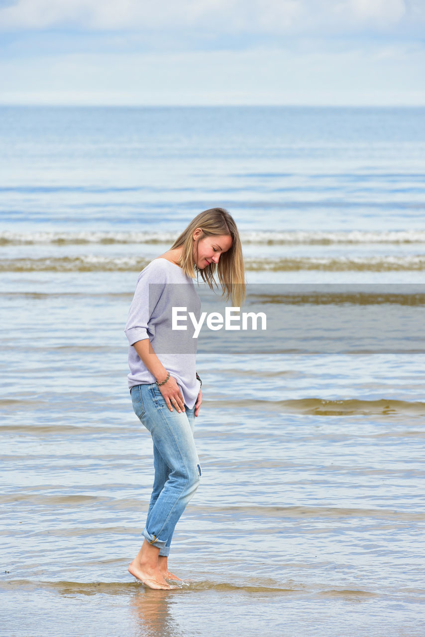 Full Length Of Young Woman Standing At Beach