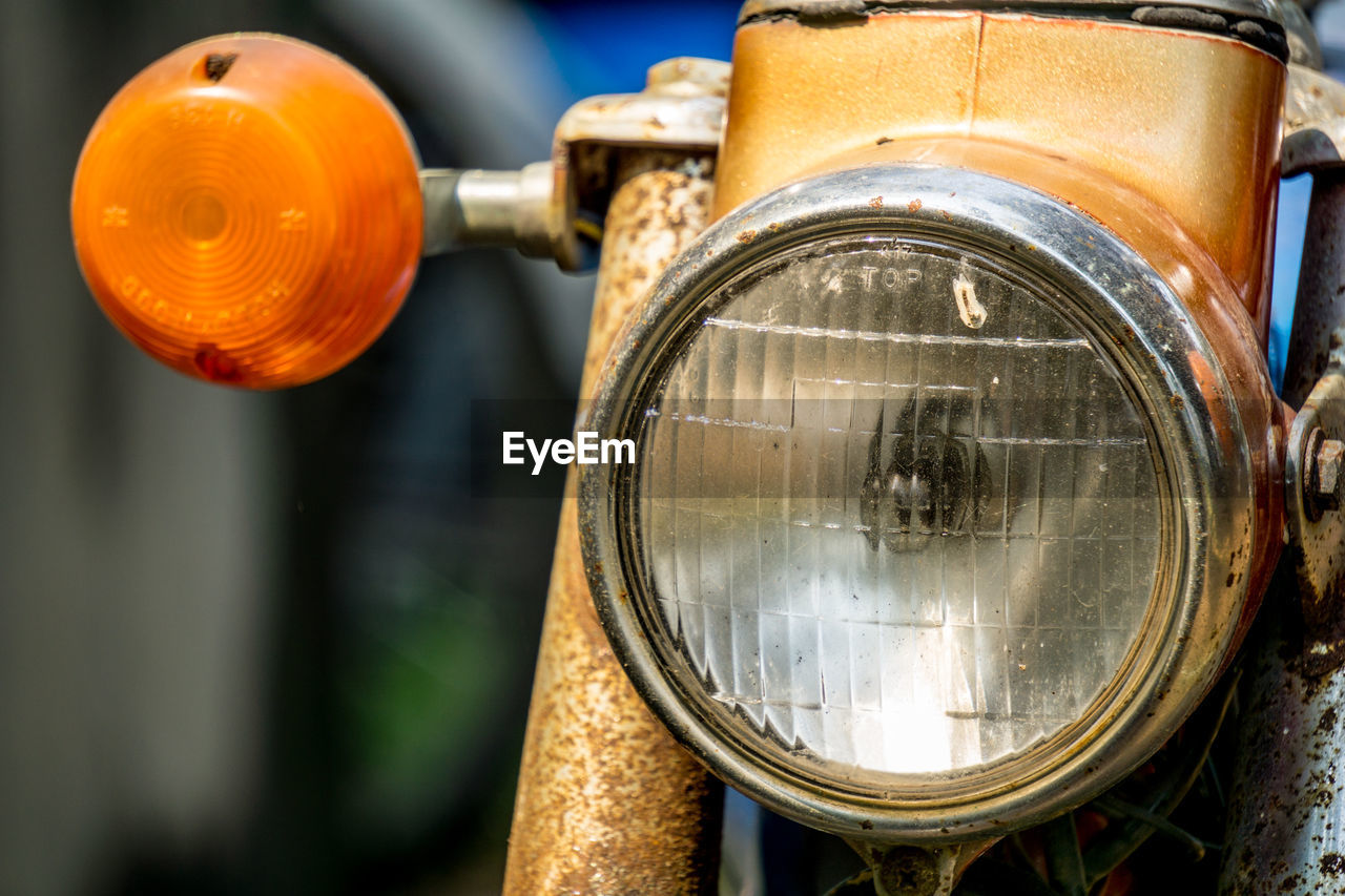 focus on foreground, close-up, metal, no people, headlight, orange color, land vehicle, technology, still life, day, lighting equipment, outdoors, mode of transportation, glass - material, nature, transportation, old, rail transportation, train