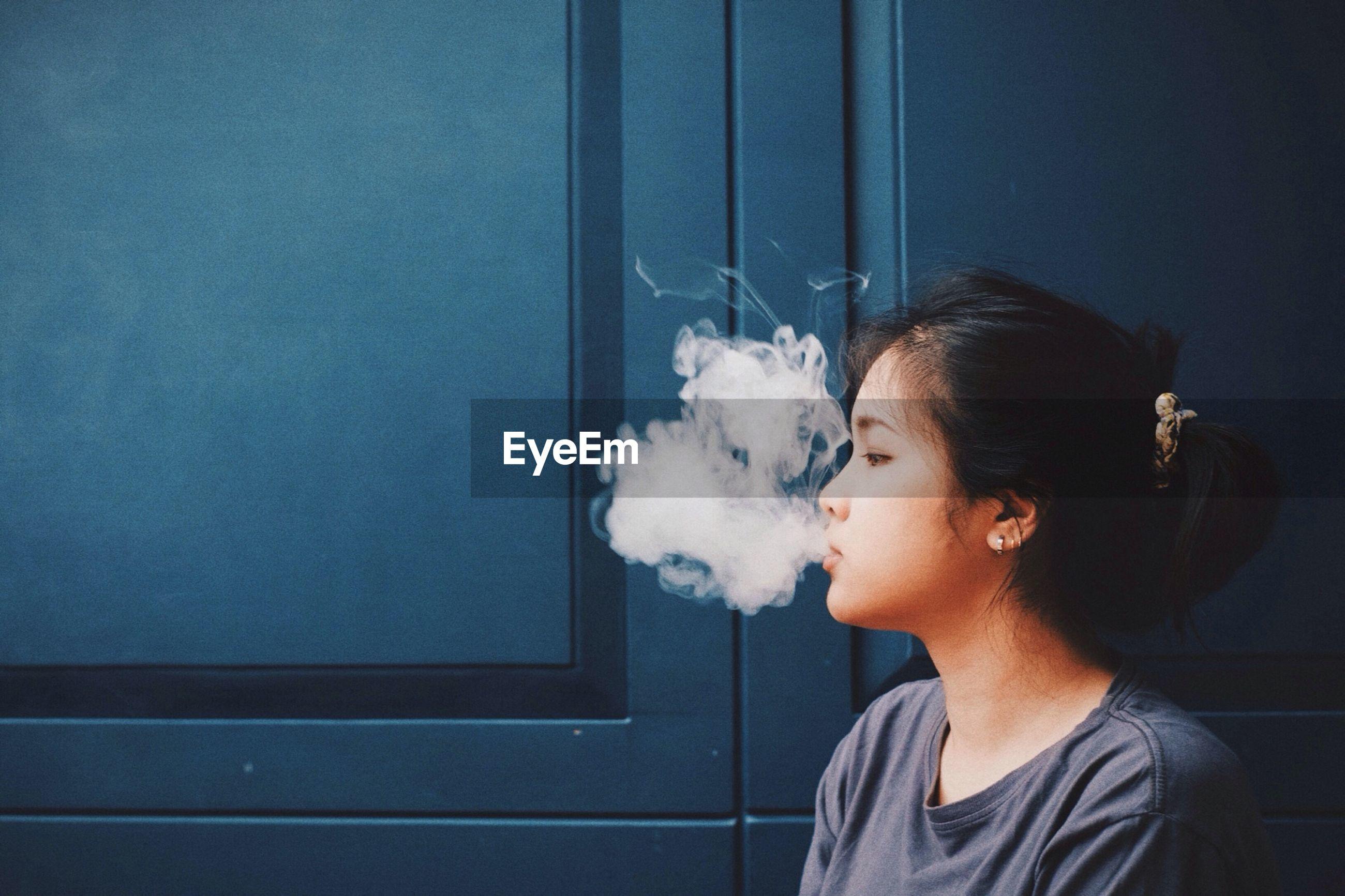 Woman smoking against door