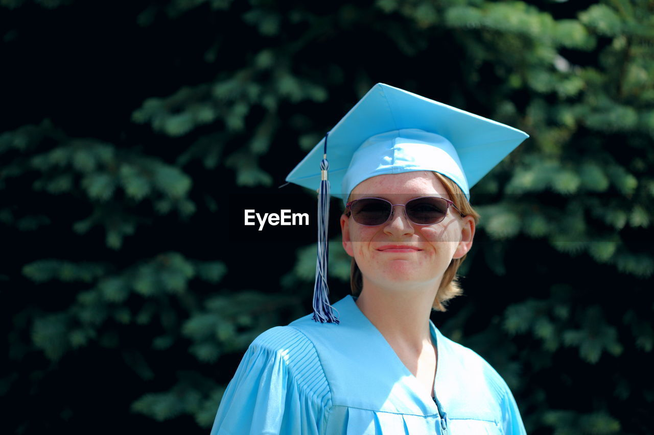 Smiling Woman With Mortarboard Against Trees