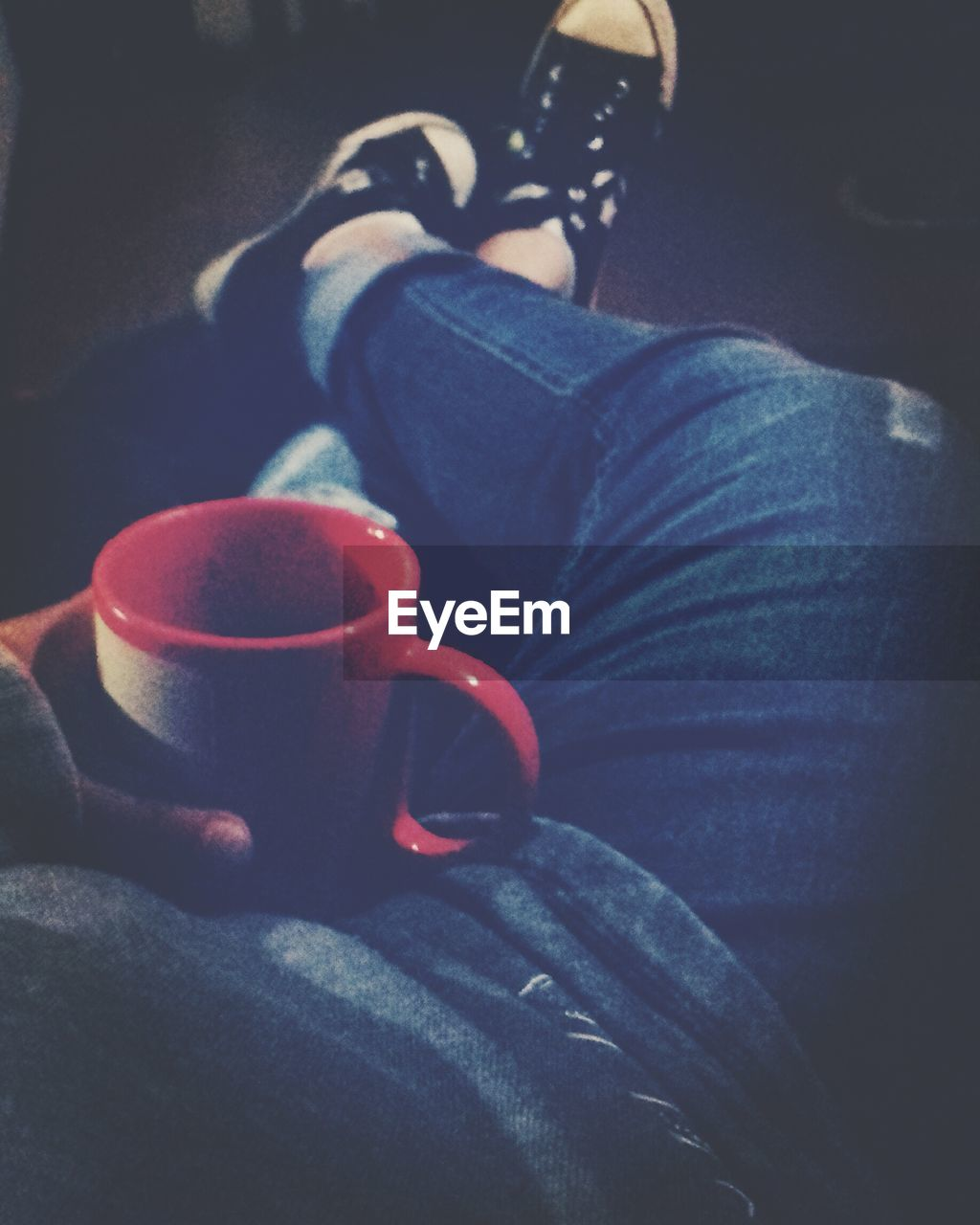 coffee cup, coffee - drink, jeans, drink, one person, refreshment, human leg, cup, food and drink, real people, holding, human body part, low section, sitting, human hand, drinking, casual clothing, indoors, tea - hot drink, red, close-up, lifestyles, men, women, relaxation, day, freshness, adult, people