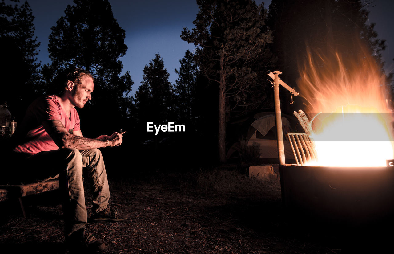 Side view of man sitting by bonfire in forest at night