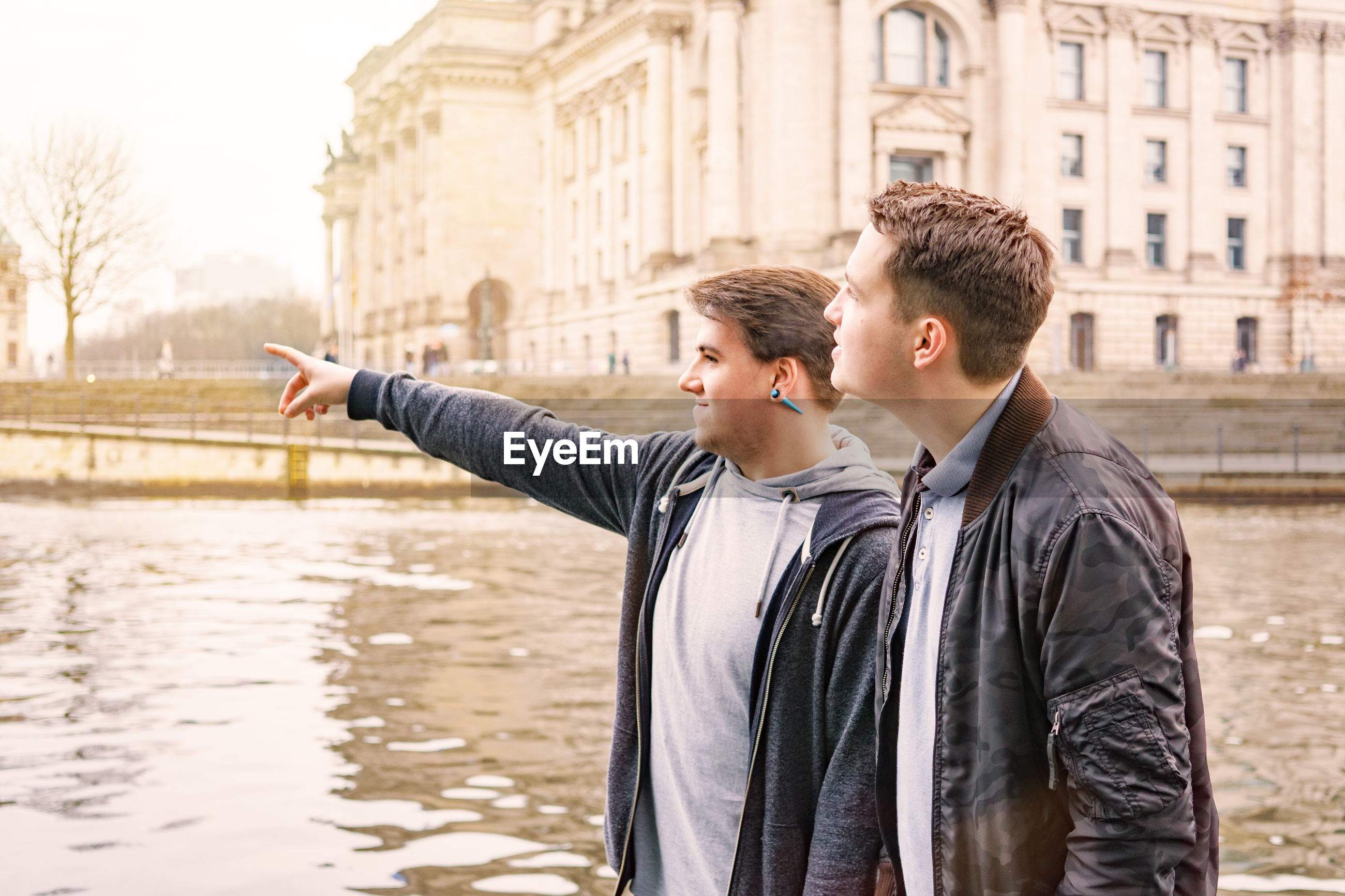 Young man with friend pointing at river in city