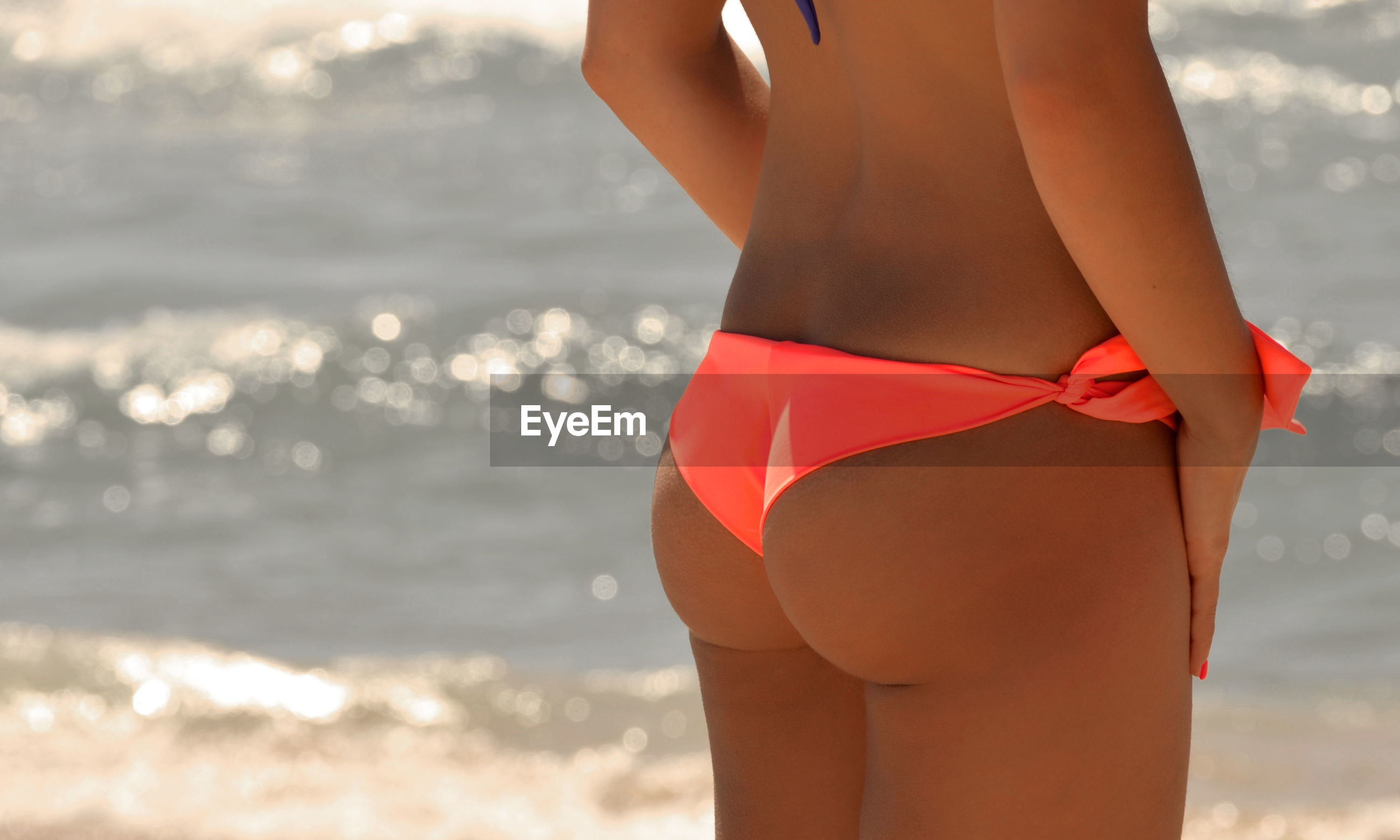 Midsection of young woman in bikini bottom standing at beach