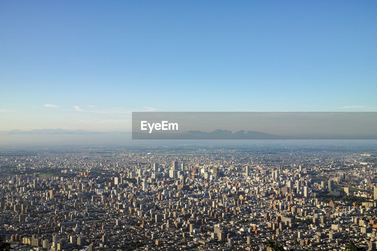 sky, cityscape, building exterior, architecture, city, built structure, crowded, crowd, building, residential district, nature, aerial view, copy space, day, travel destinations, high angle view, sunlight, clear sky, outdoors, skyscraper, office building exterior, townscape