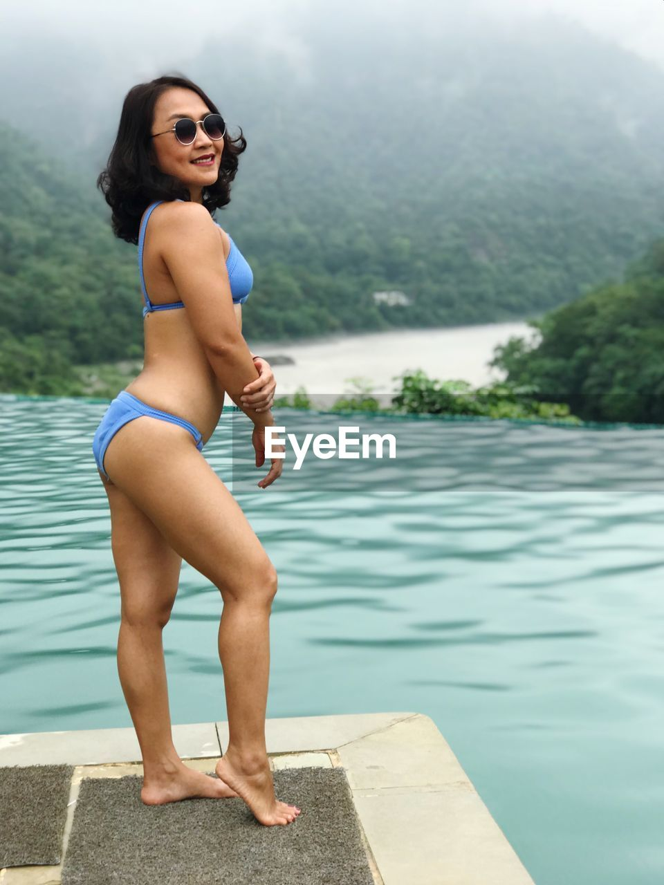 one person, water, swimwear, leisure activity, lifestyles, young adult, real people, clothing, full length, standing, side view, nature, young women, women, day, bikini, lake, beautiful woman, swimming pool, outdoors