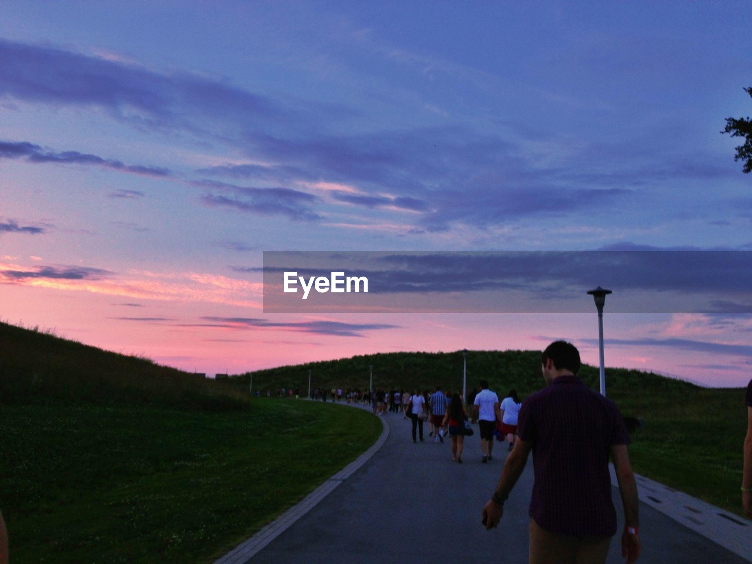Rear view of people walking on road along landscape