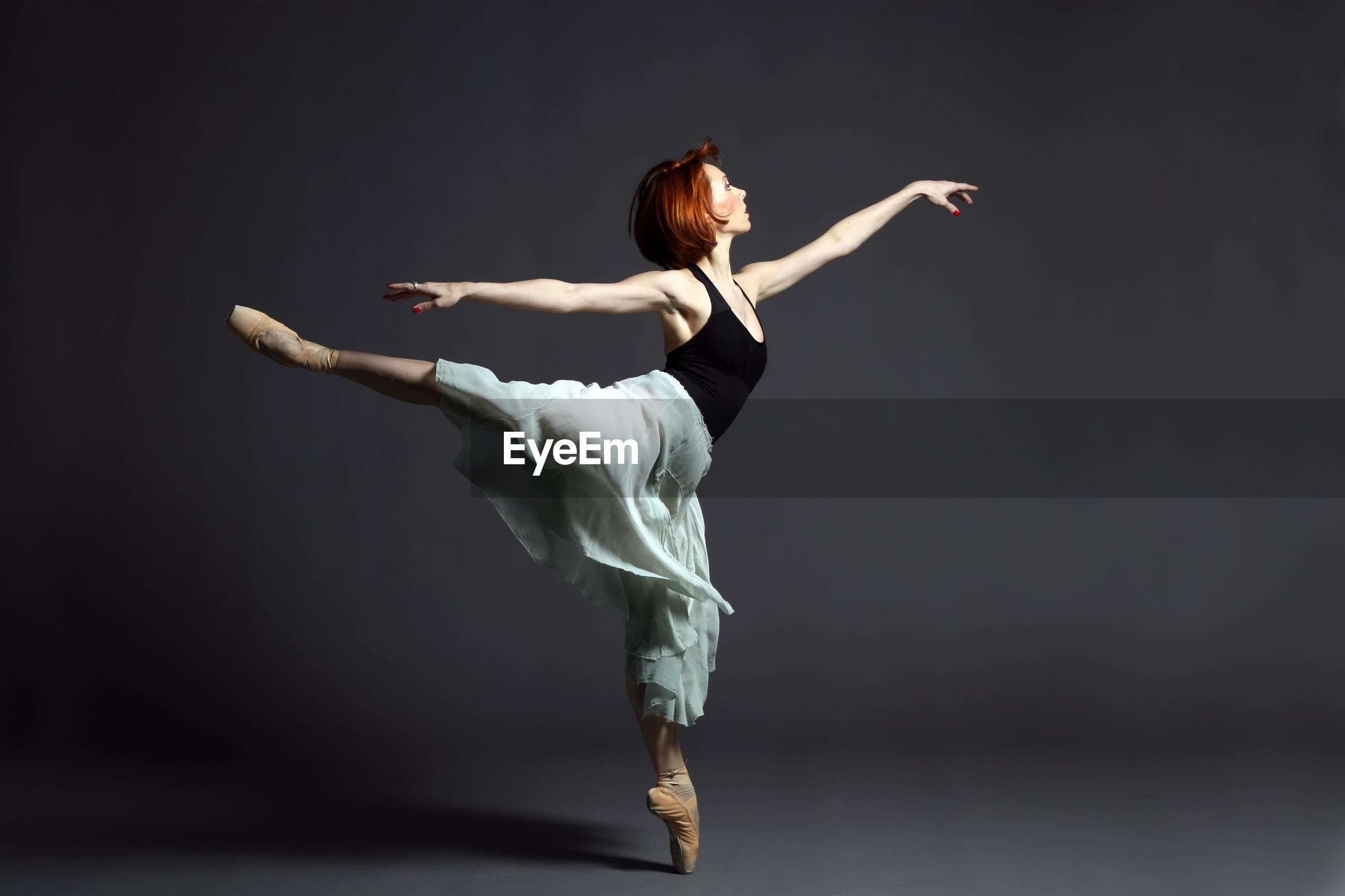 Ballerina dancing against gray backdrop