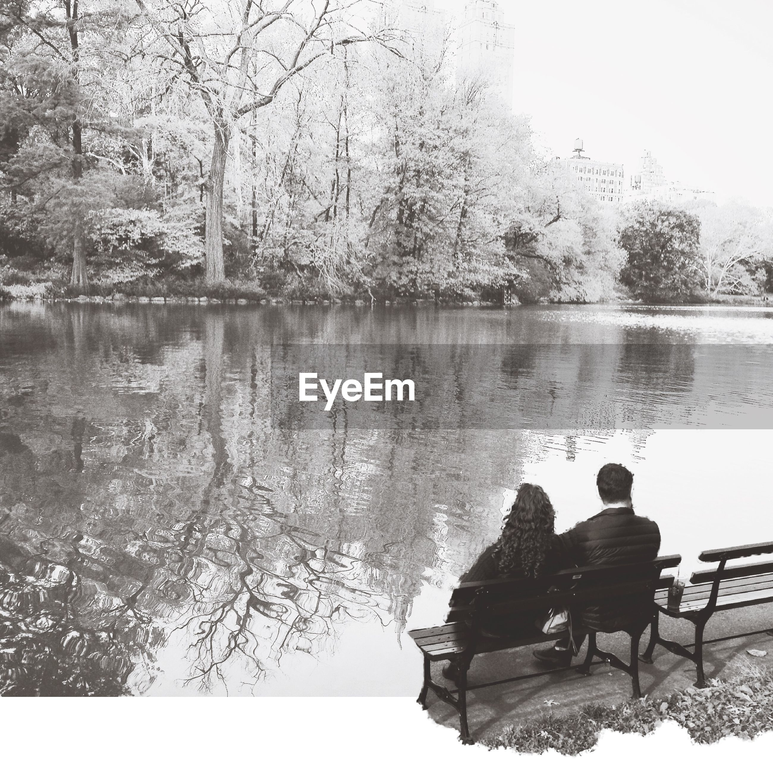 Couple sitting on bench in lakeshore