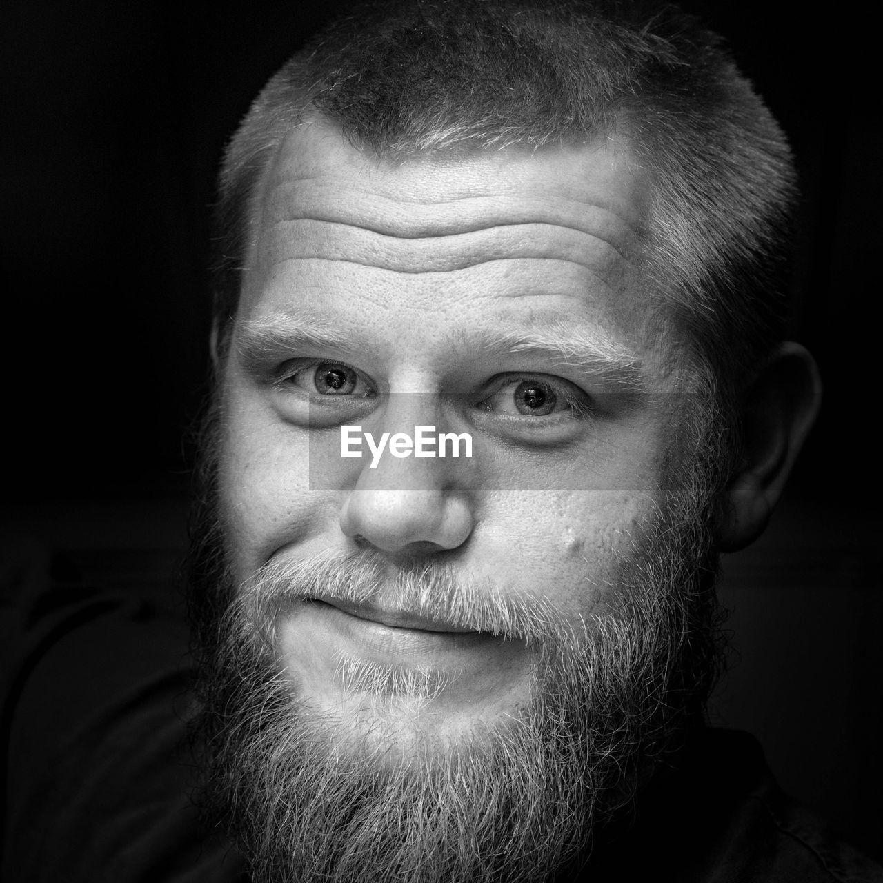 Close-up portrait of man smiling against black background