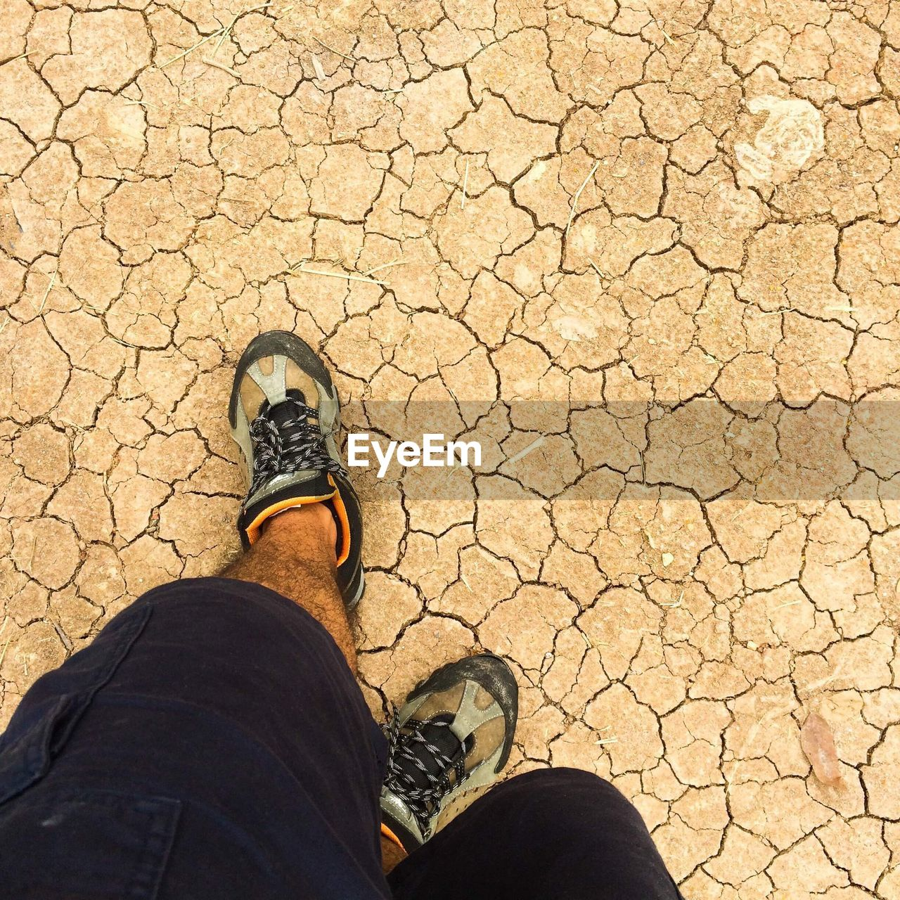 Low section of man standing on cracked land