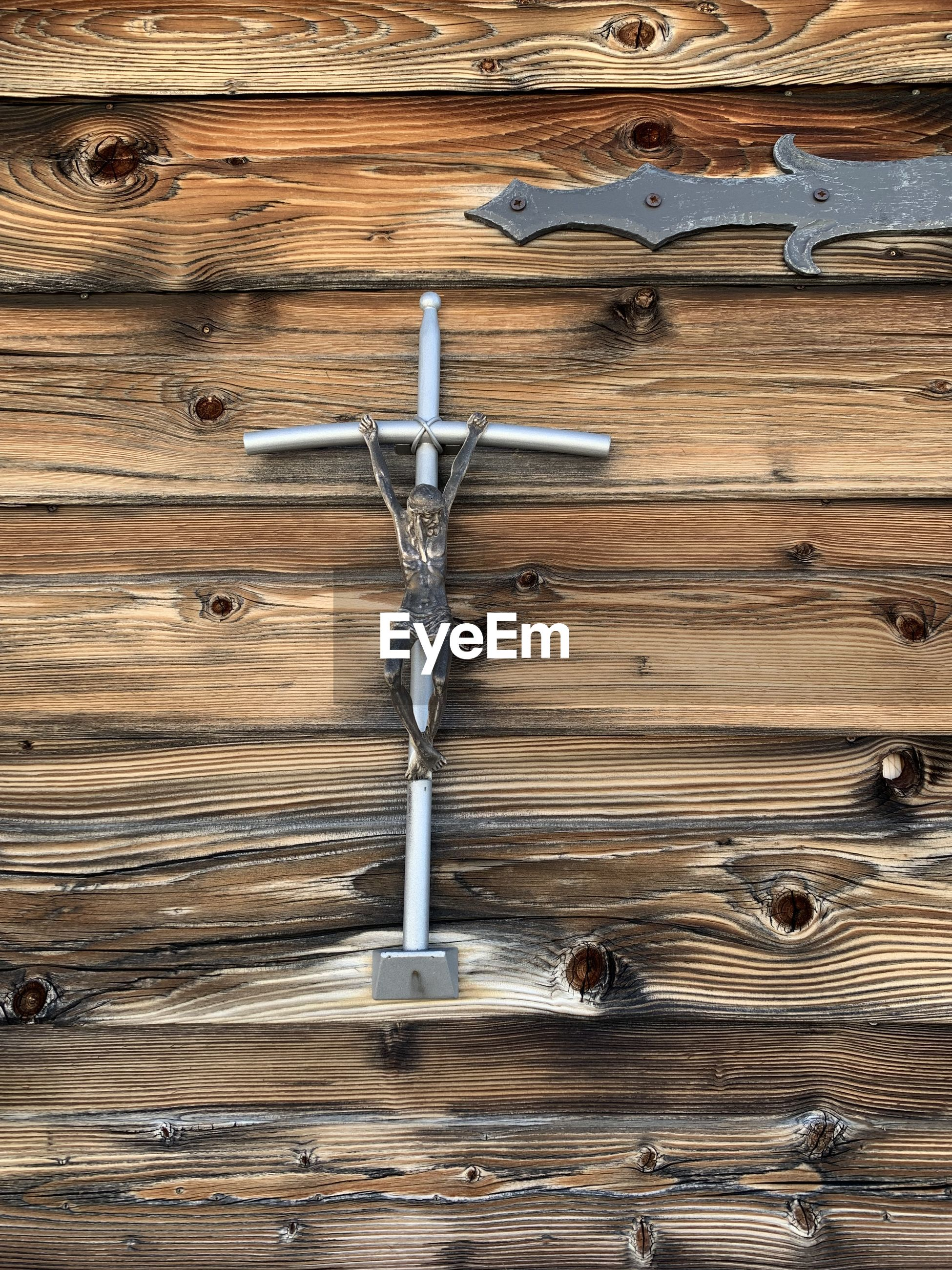Close-up of jesus figurine hanging against wooden wall