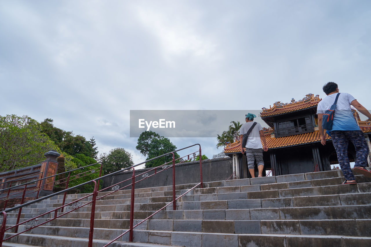 steps, railing, steps and staircases, staircase, real people, low angle view, built structure, men, sky, cloud - sky, architecture, day, lifestyles, outdoors, women, full length, building exterior, tree, people