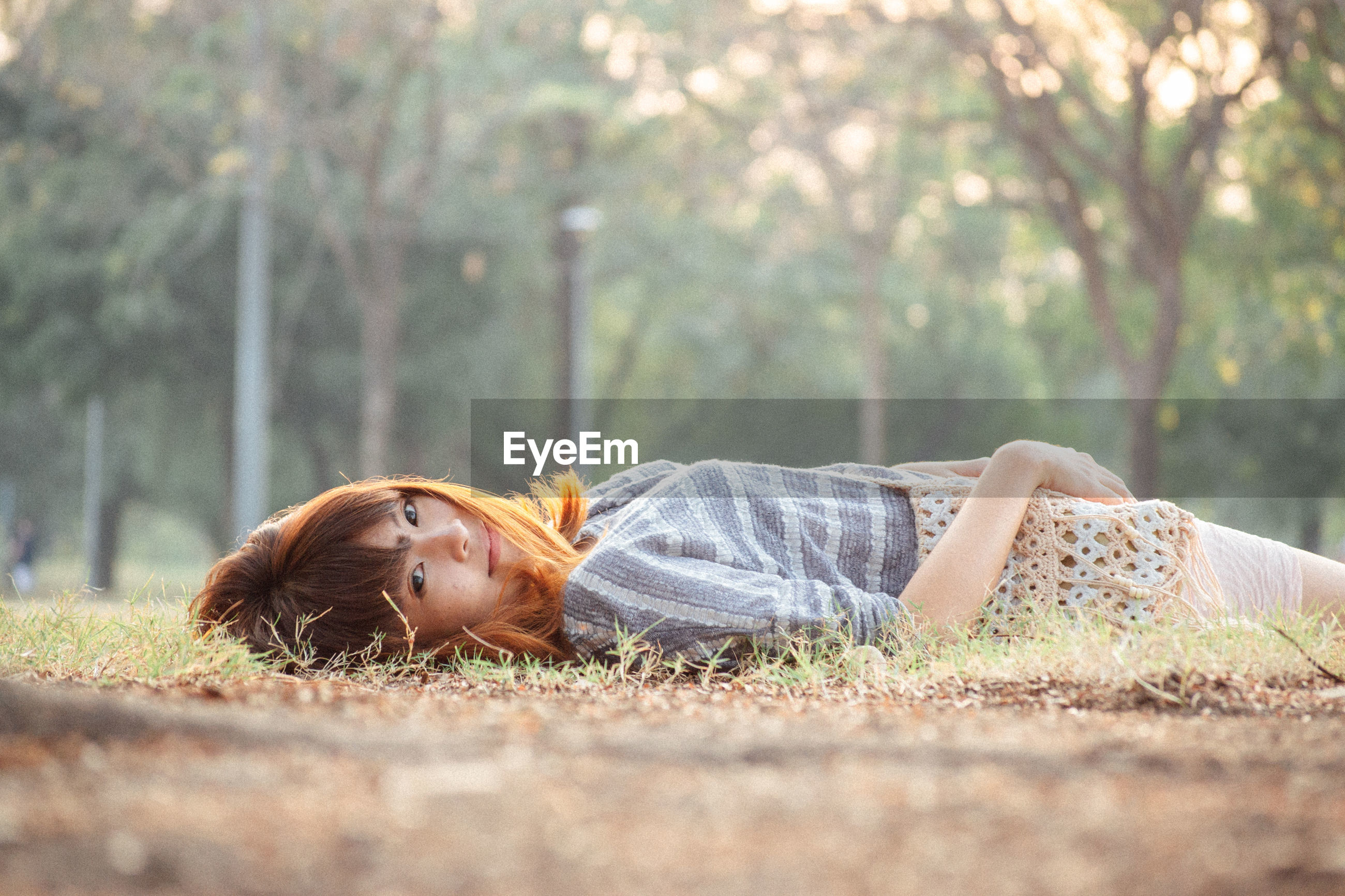 Full length of young woman lying on land