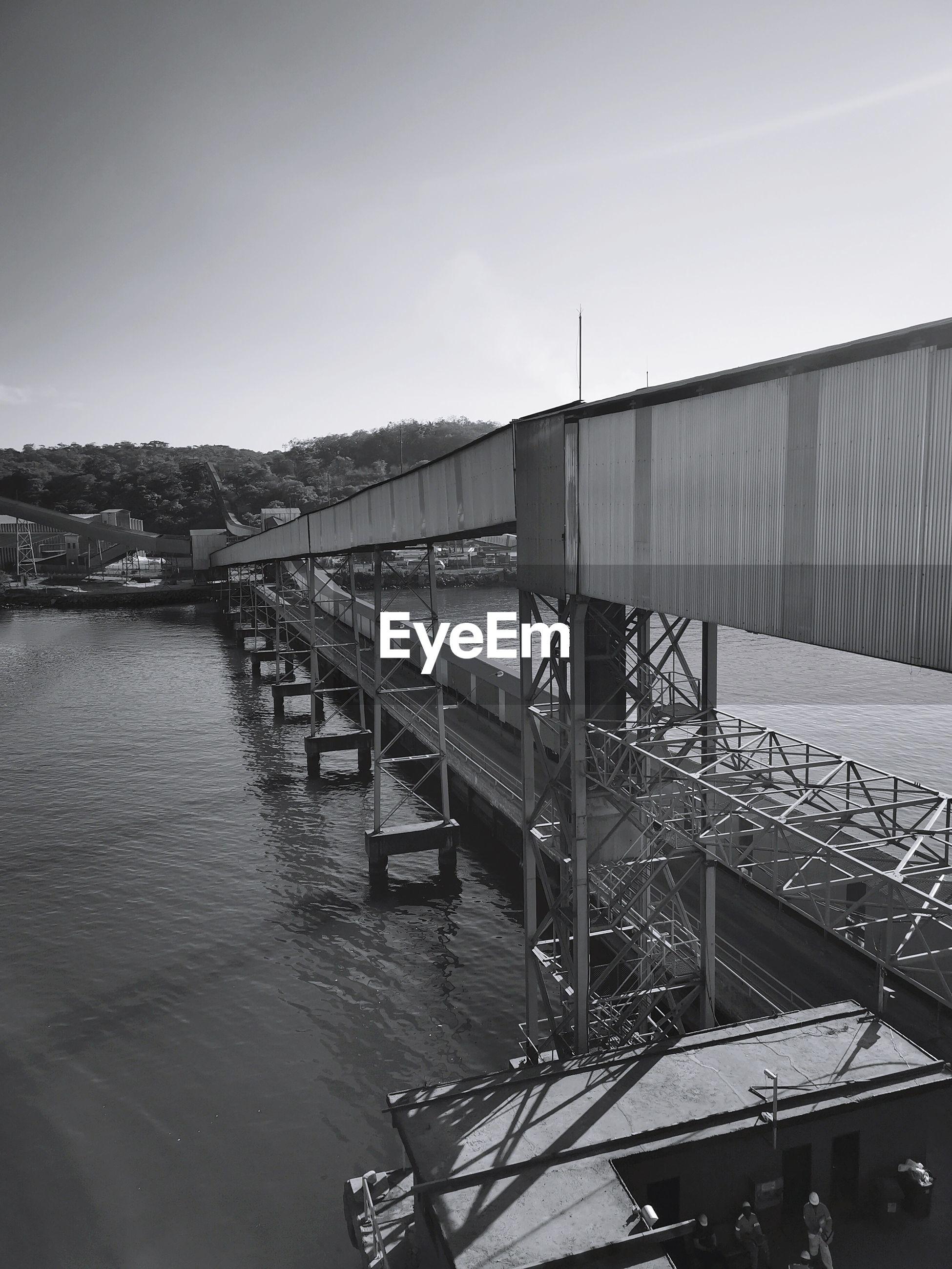Bridge over a bah by buildings against clear sky