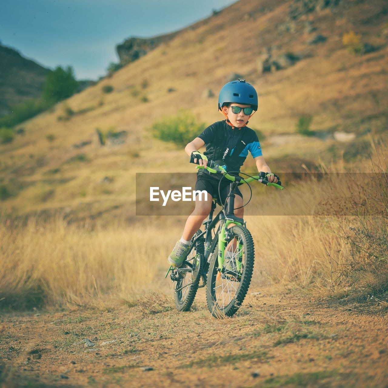 one person, real people, field, headwear, helmet, land, leisure activity, lifestyles, riding, transportation, bicycle, ride, day, nature, land vehicle, plant, mode of transportation, child, outdoors