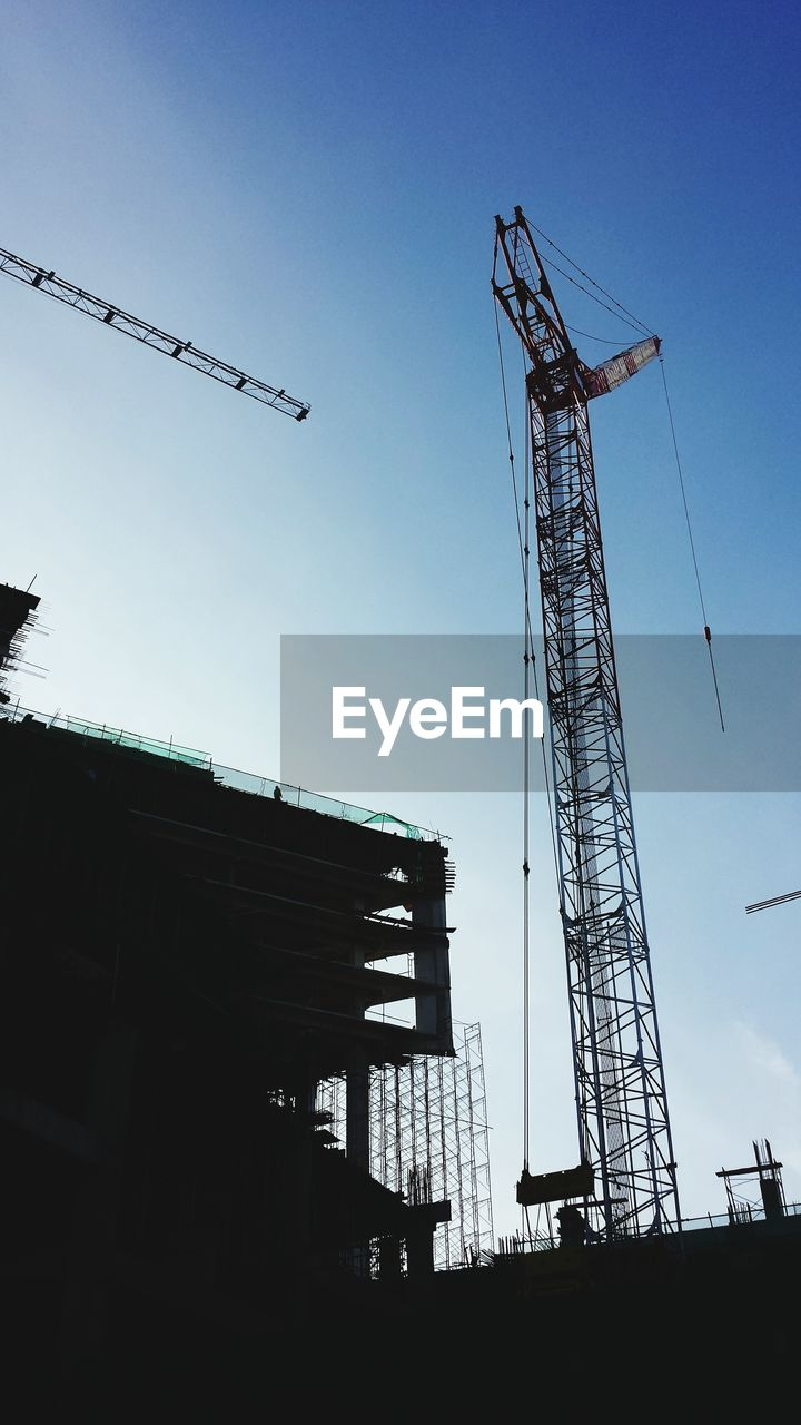 construction site, low angle view, development, architecture, built structure, crane - construction machinery, silhouette, crane, no people, clear sky, outdoors, industry, day, sky