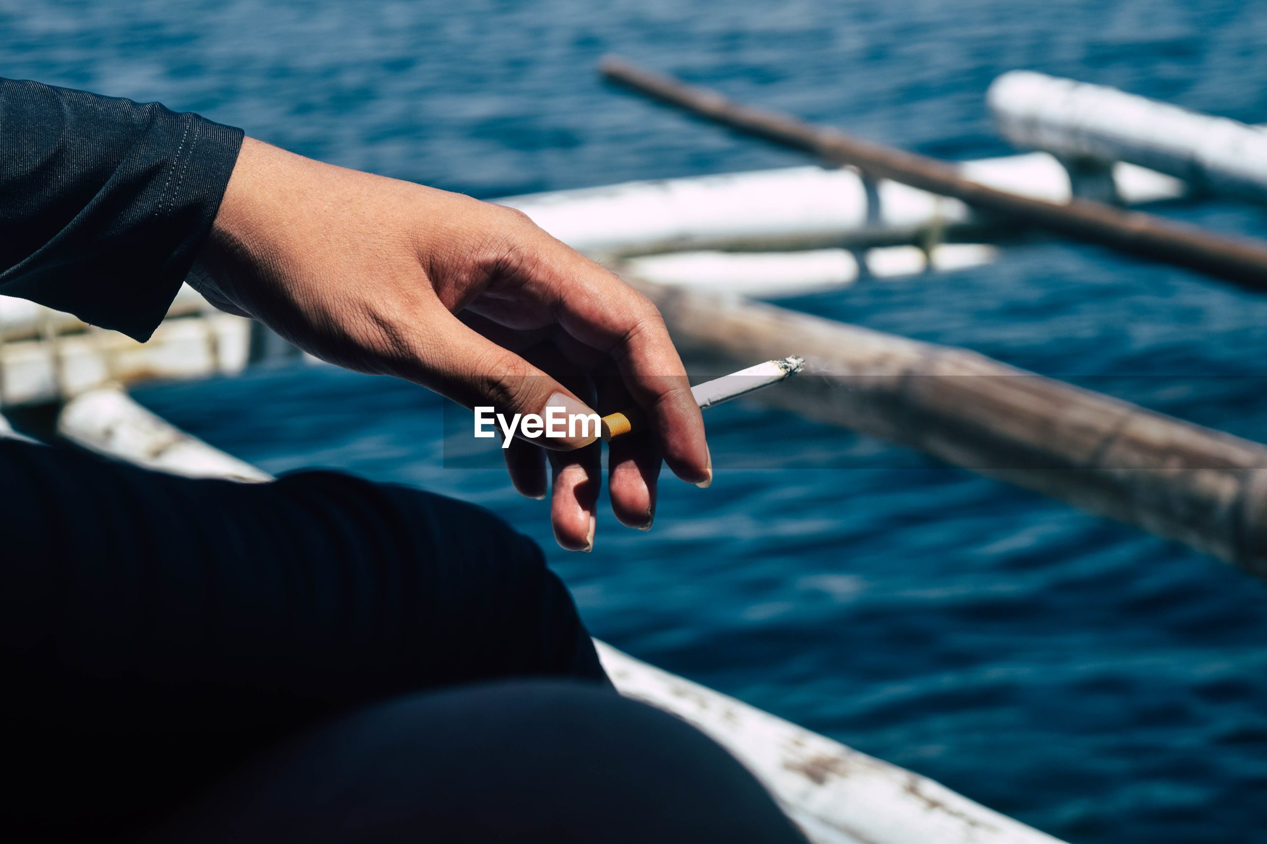 Midsection of person holding cigarette in sea