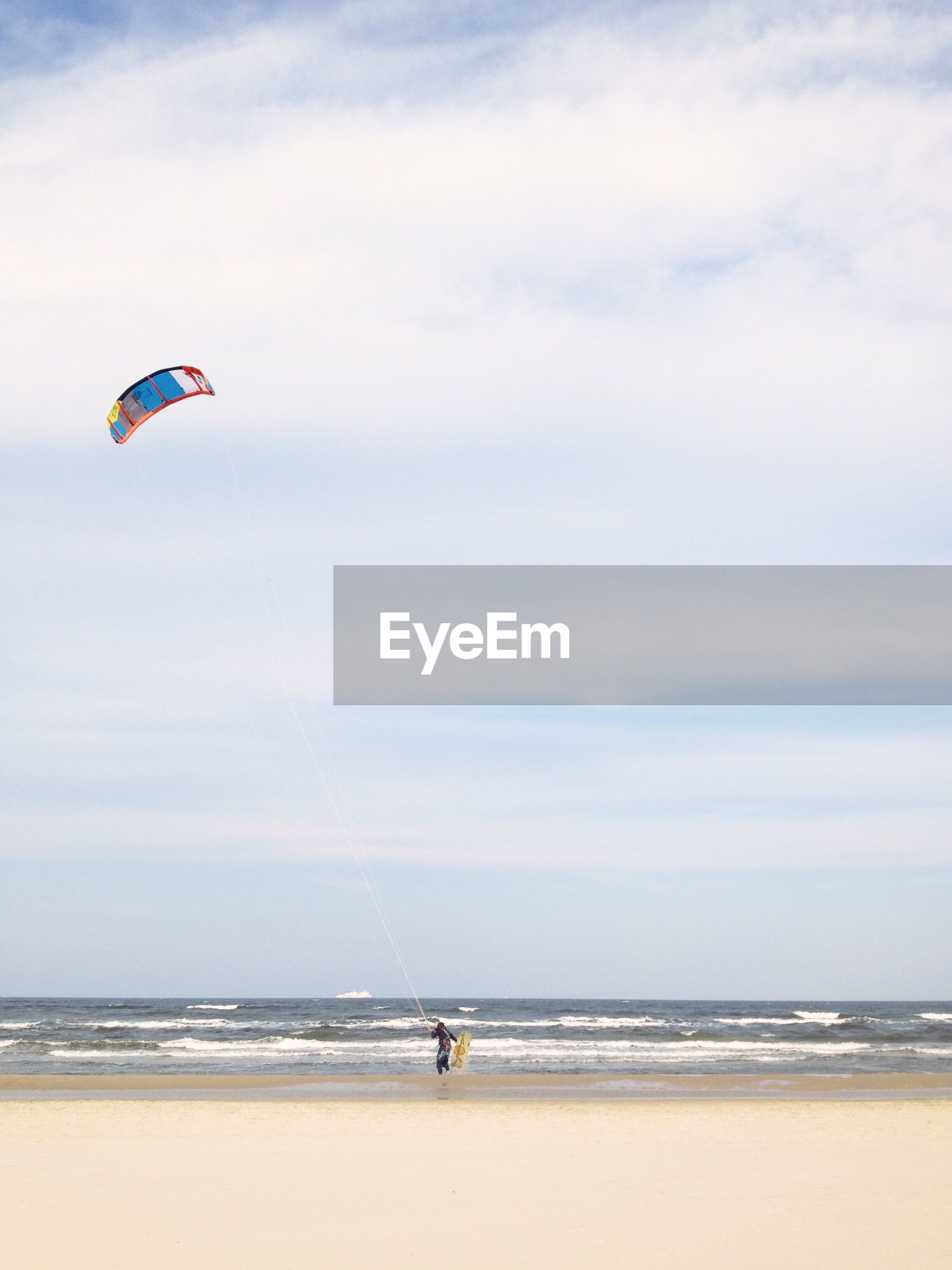 sea, sky, horizon over water, water, extreme sports, horizon, adventure, sport, cloud - sky, beach, real people, land, leisure activity, parachute, paragliding, beauty in nature, nature, scenics - nature, lifestyles, kiteboarding, outdoors