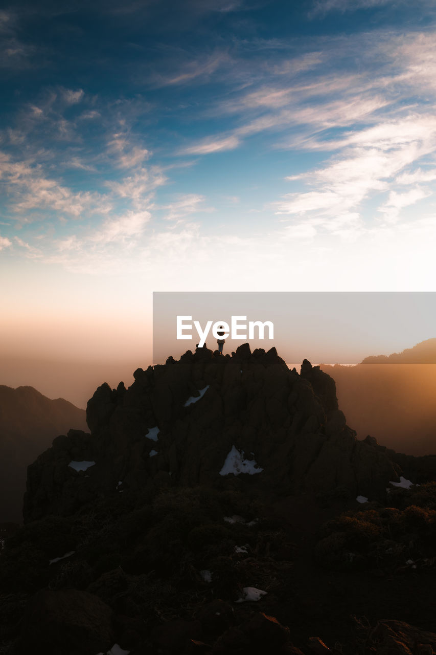 Silhouette rocks on rock formation against sky during sunset