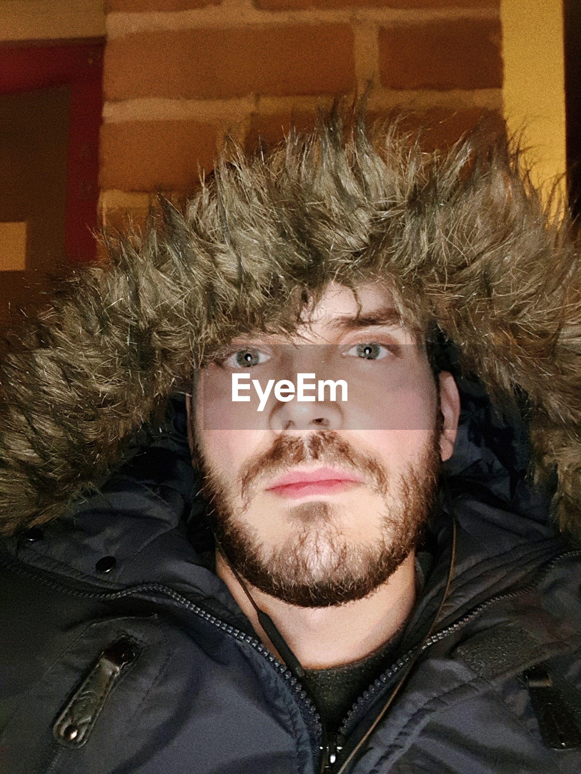 Portrait of man wearing fur coat at home