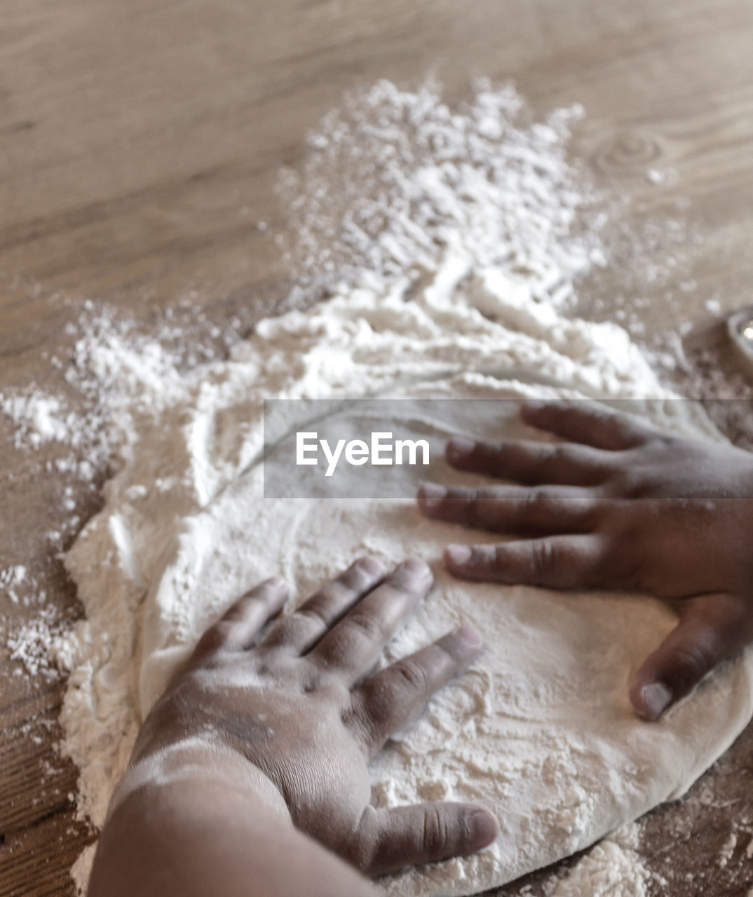 Cropped Hands On Kid Flattening Dough On Table