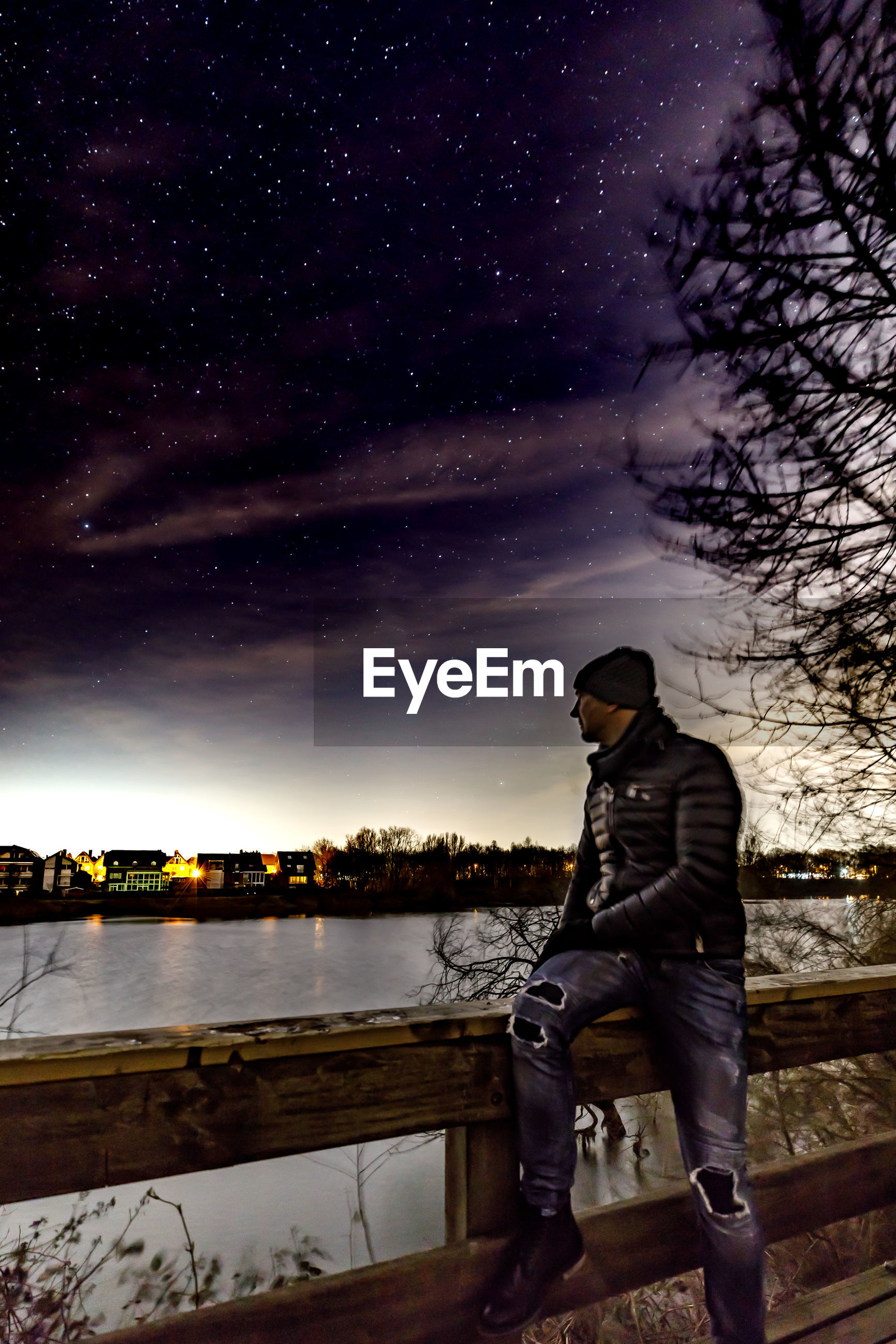 Man sitting on railing by lake against star field
