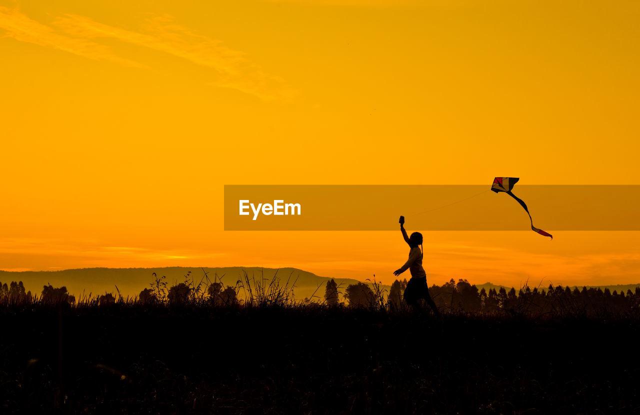 Side view of girl flying kite against orange sky