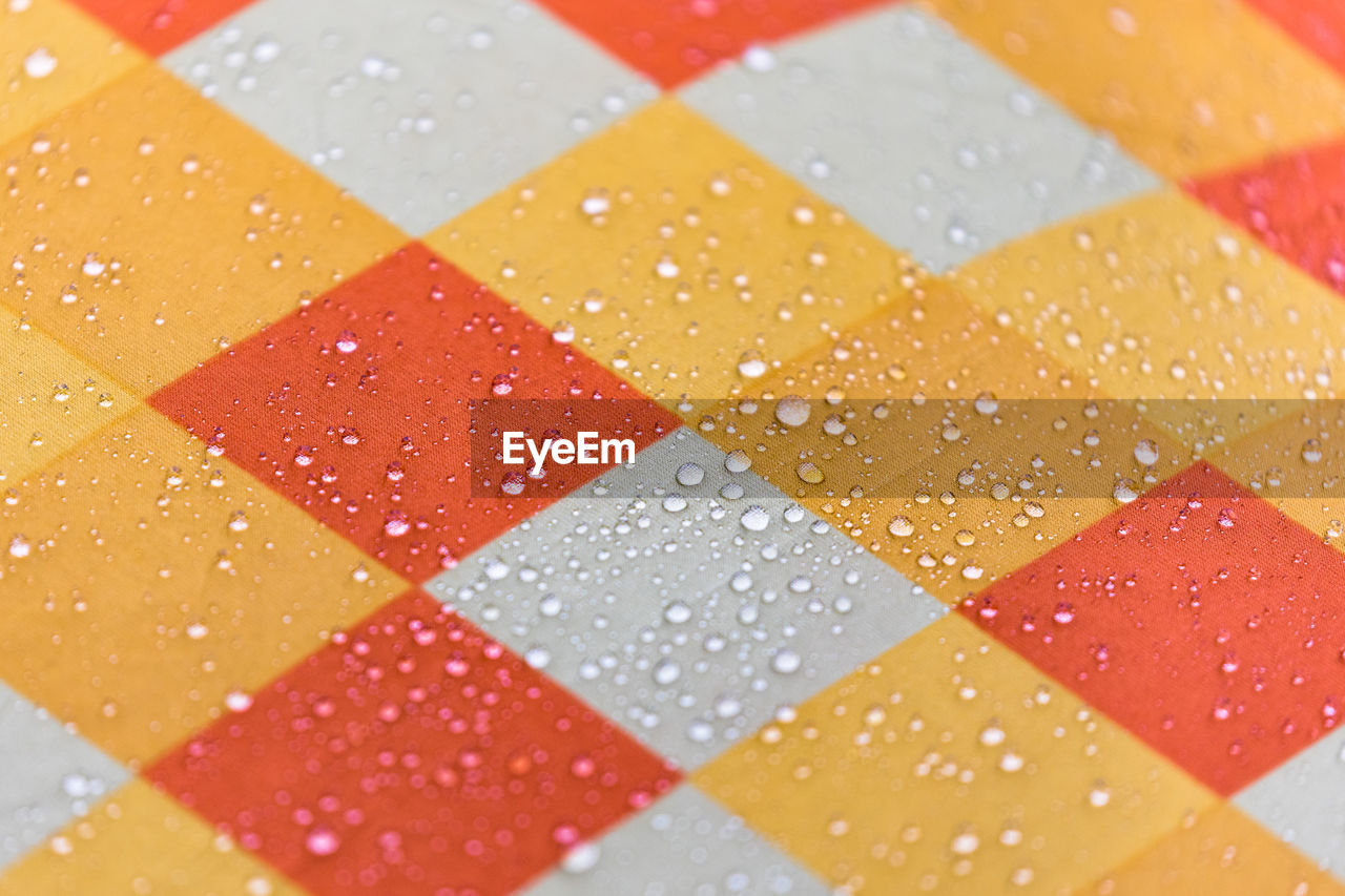 Full Frame Shot Of Checked Pattern Fabric With Water Drops