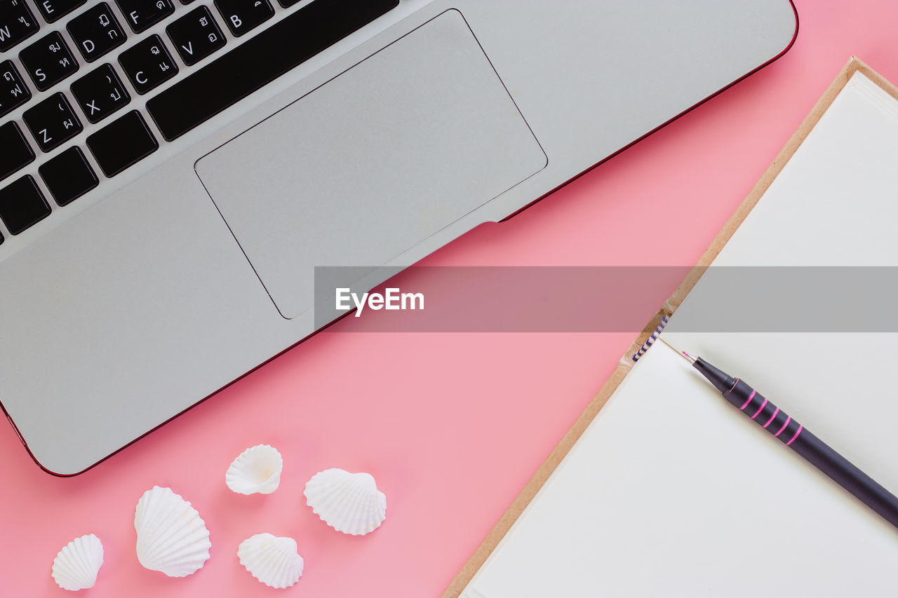computer, laptop, indoors, wireless technology, high angle view, technology, communication, connection, no people, still life, computer equipment, keyboard, table, computer keyboard, close-up, pink color, portable information device, paper, white color, directly above, computer key