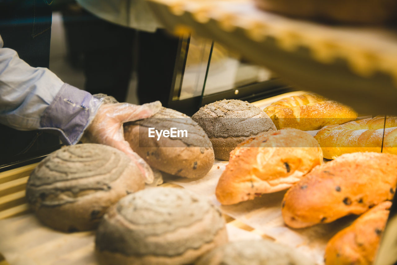 food, food and drink, freshness, one person, human hand, hand, baked, bread, indoors, human body part, real people, selective focus, bakery, occupation, close-up, store, indulgence, preparation, sweet food, preparing food, baking sheet, temptation, human limb, finger