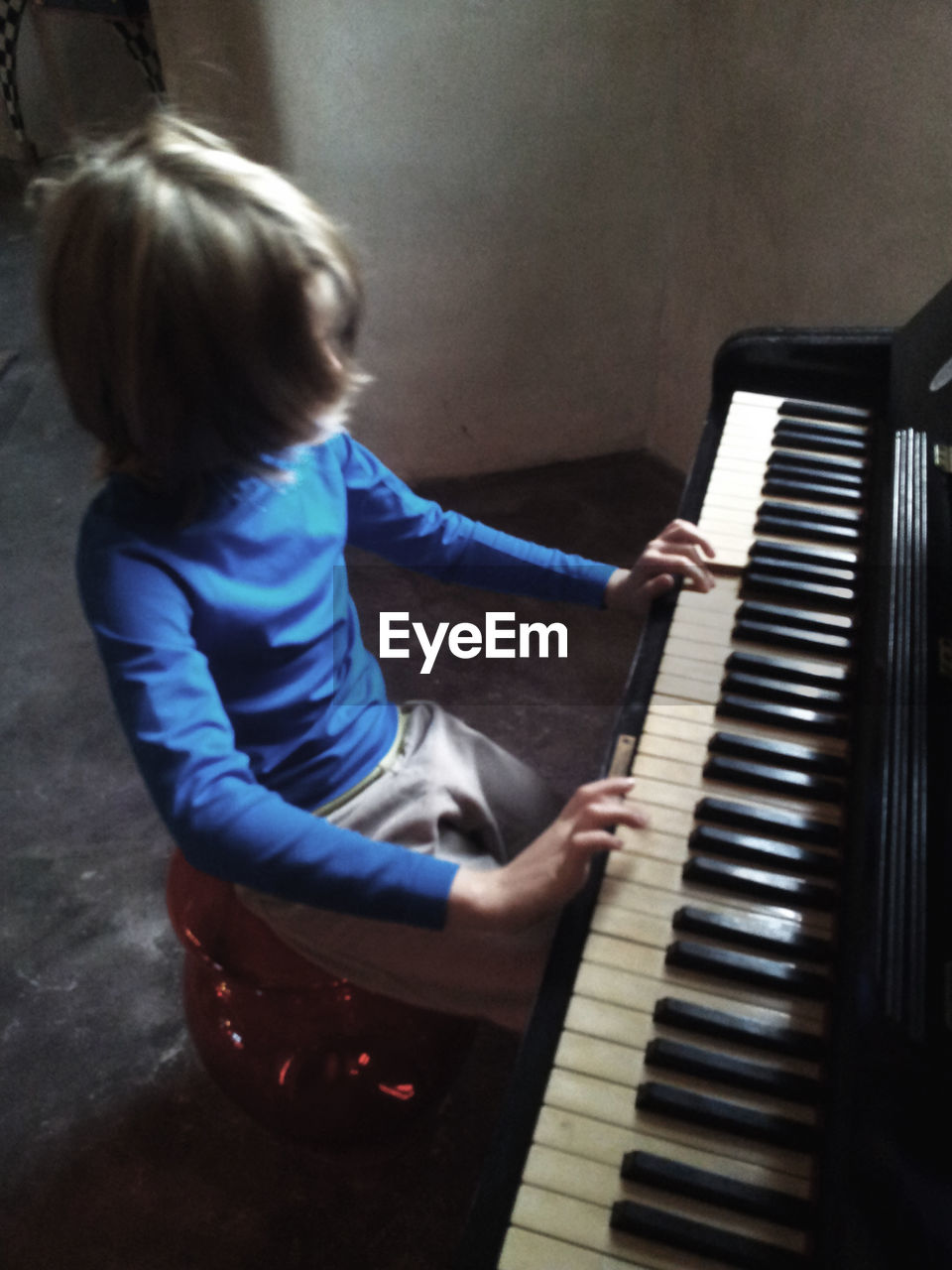 High angle view of girl playing piano at home