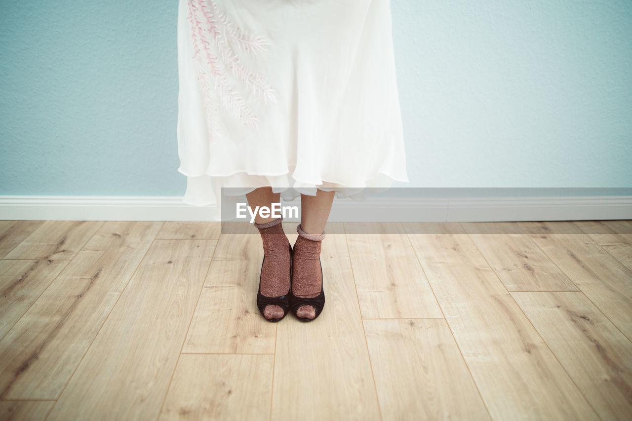 Low Section Of Woman Standing On Hardwood Floor