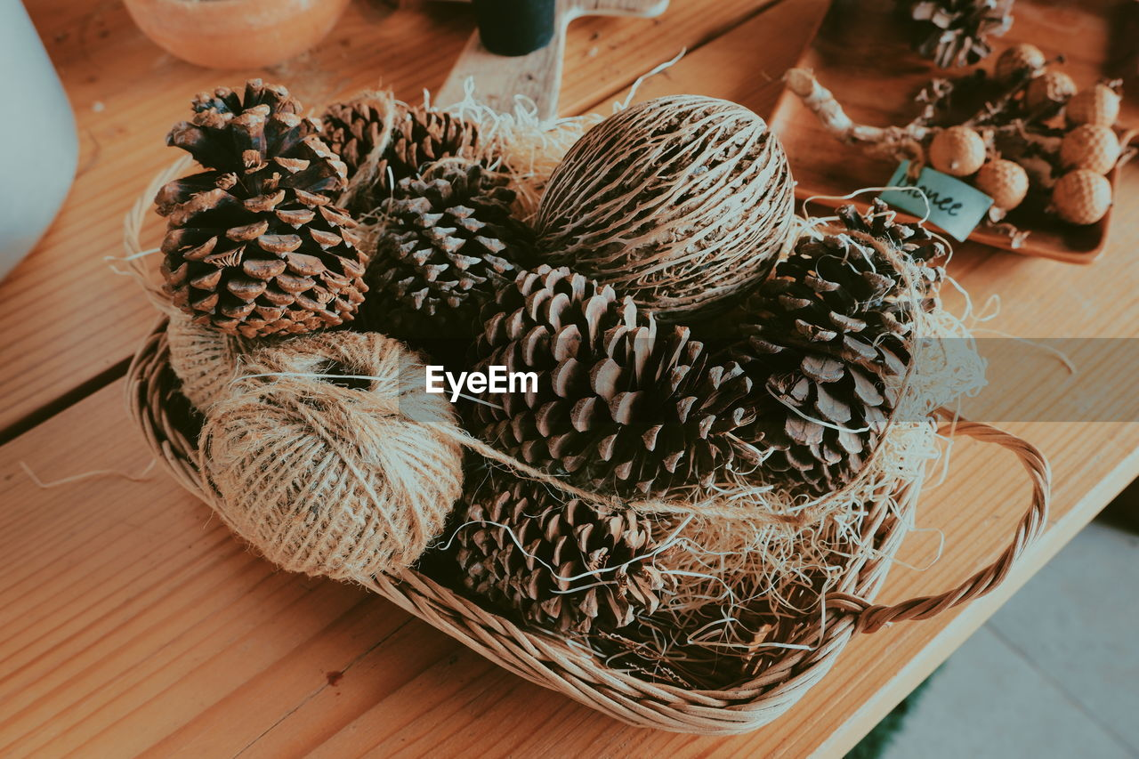 HIGH ANGLE VIEW OF PINE CONE IN BASKET ON TABLE