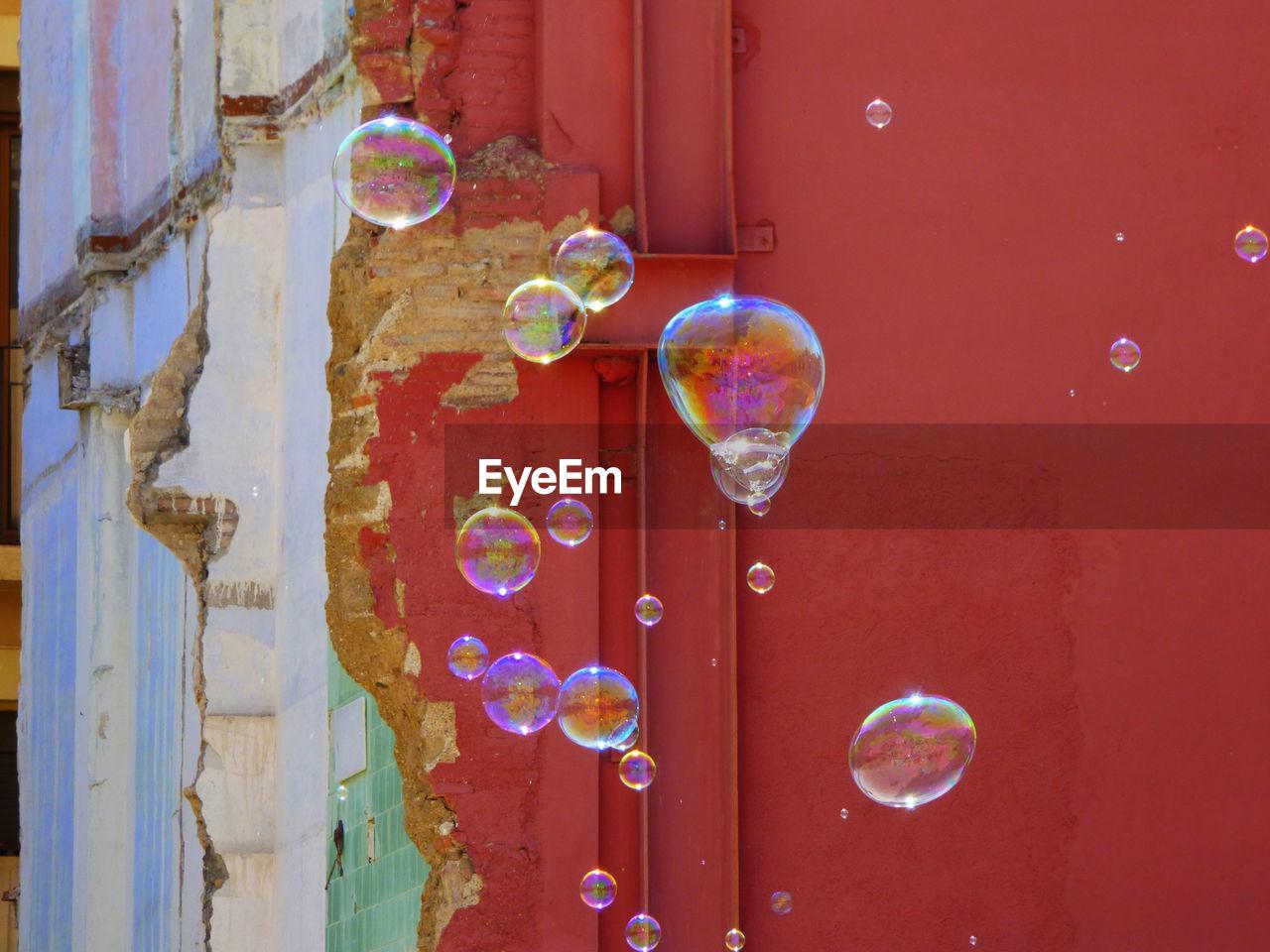 bubble, vulnerability, day, no people, fragility, transparent, mid-air, architecture, built structure, close-up, building exterior, multi colored, outdoors, door, entrance, nature, building, shape, soap sud