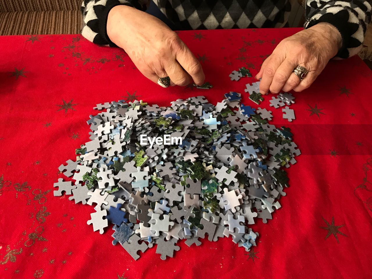 Midsection Of Senior Woman Assembling Jigsaw Puzzle Pieces On Table