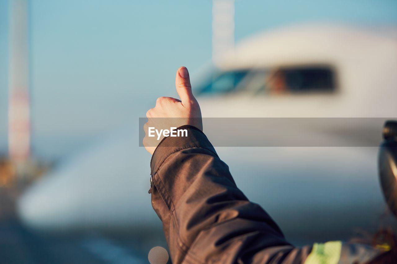 Cropped Image Of Man Gesturing Against Airplane At Airport Runway