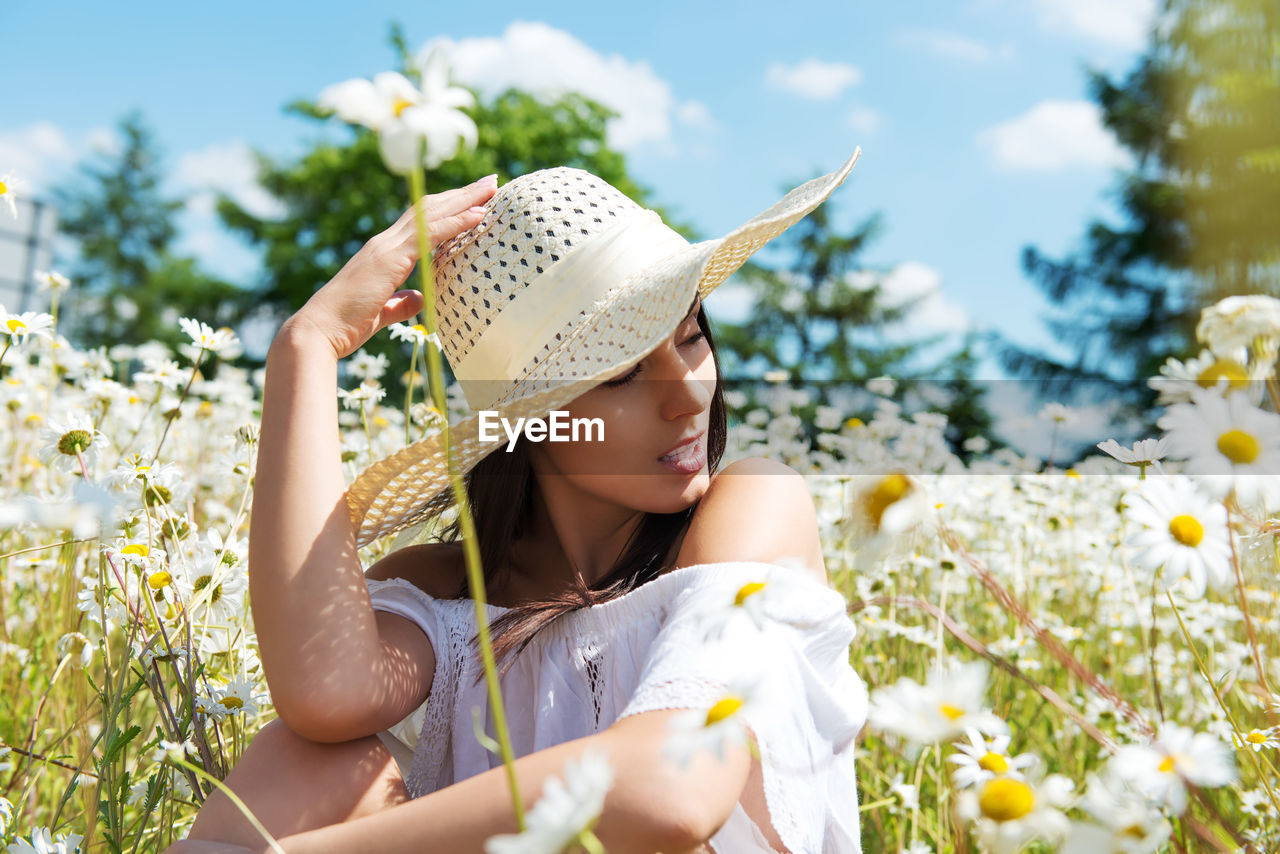 Beautiful Woman Wearing Sun Hat Sitting Amidst White Daisy Flowers On Field Against Sky