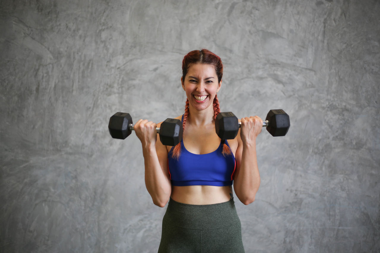 Portrait Of Smiling Young Woman Lifting Dumbbells On Eyeem