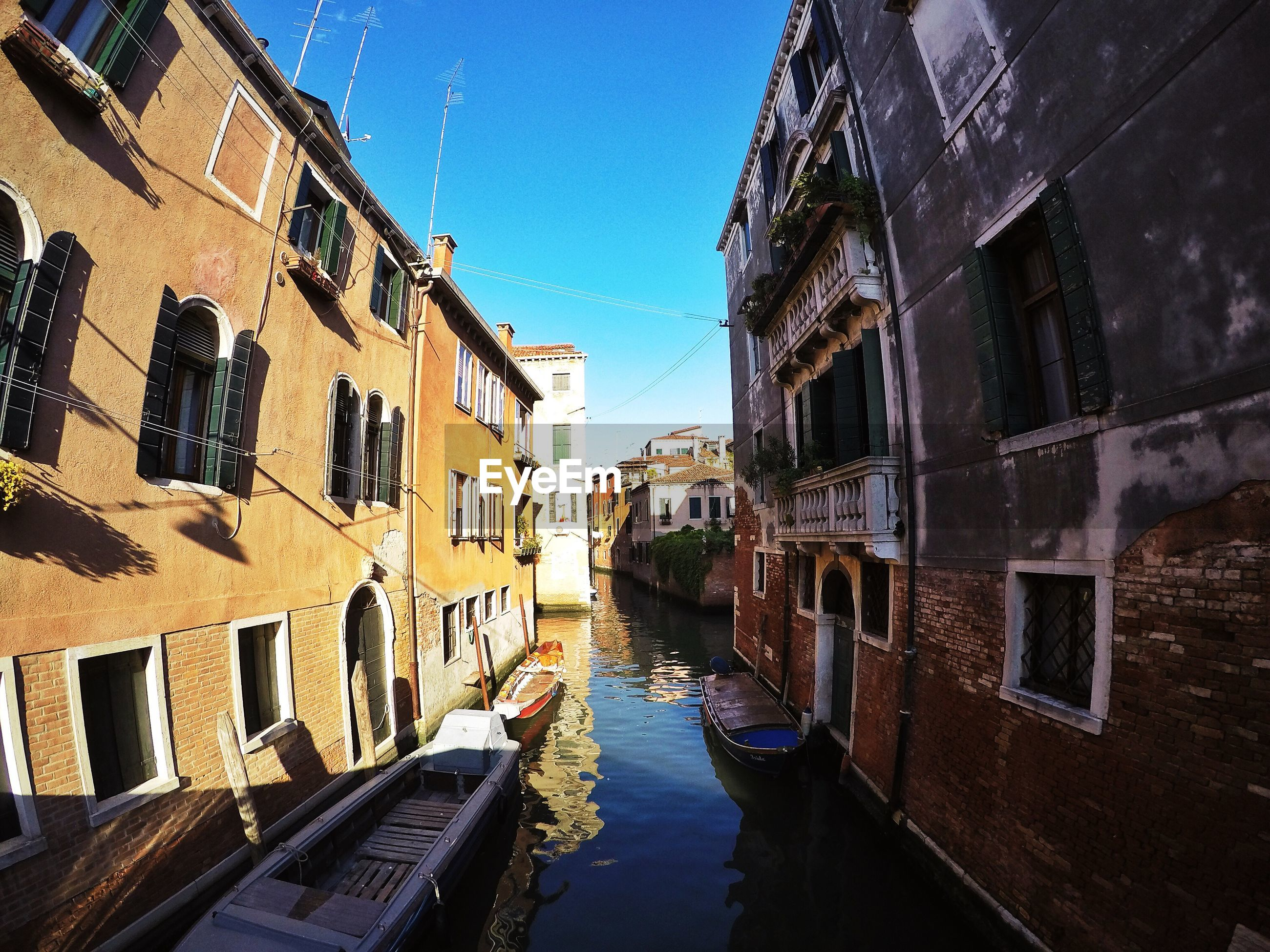 architecture, built structure, building exterior, water, canal, residential building, residential structure, building, waterfront, reflection, city, house, blue, diminishing perspective, sky, day, outdoors, narrow, sunlight, town