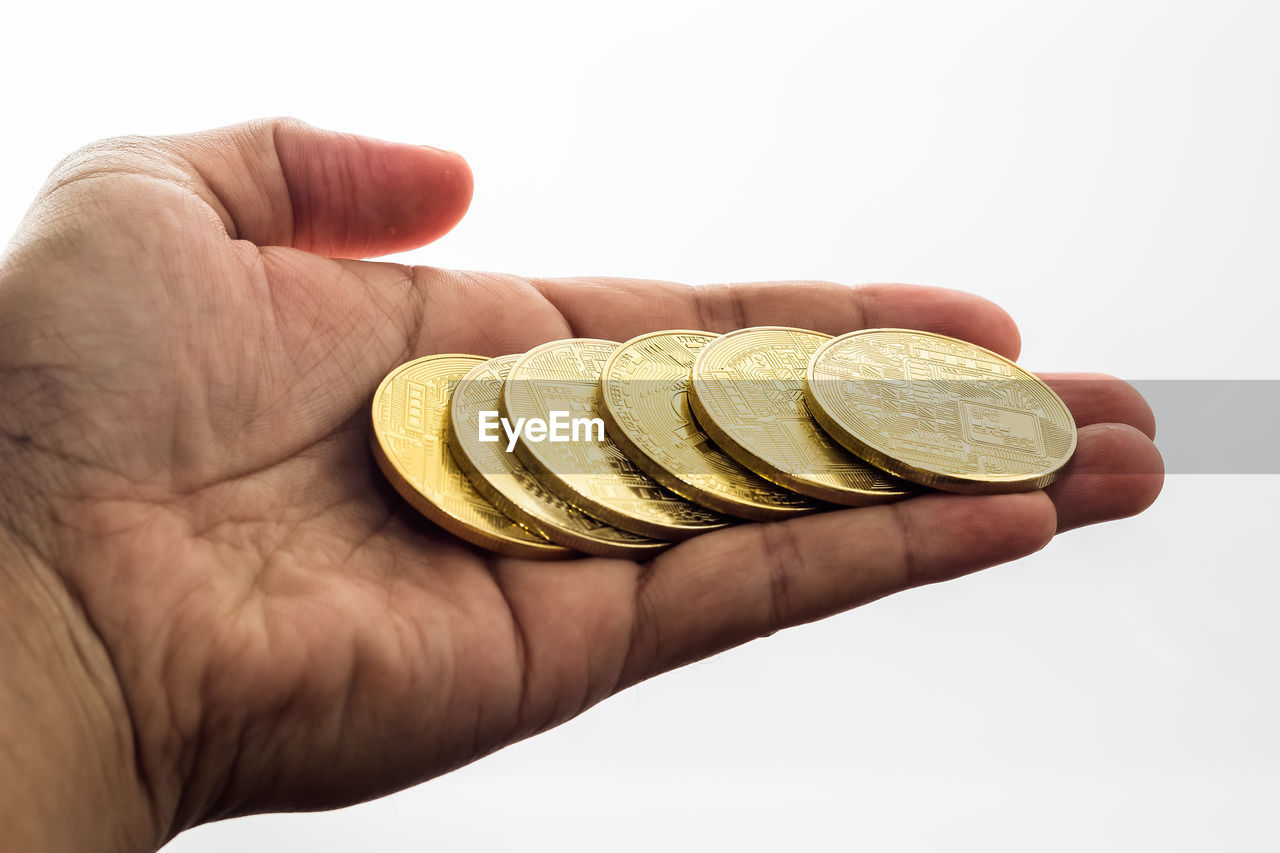 Cropped hand holding coins on white background
