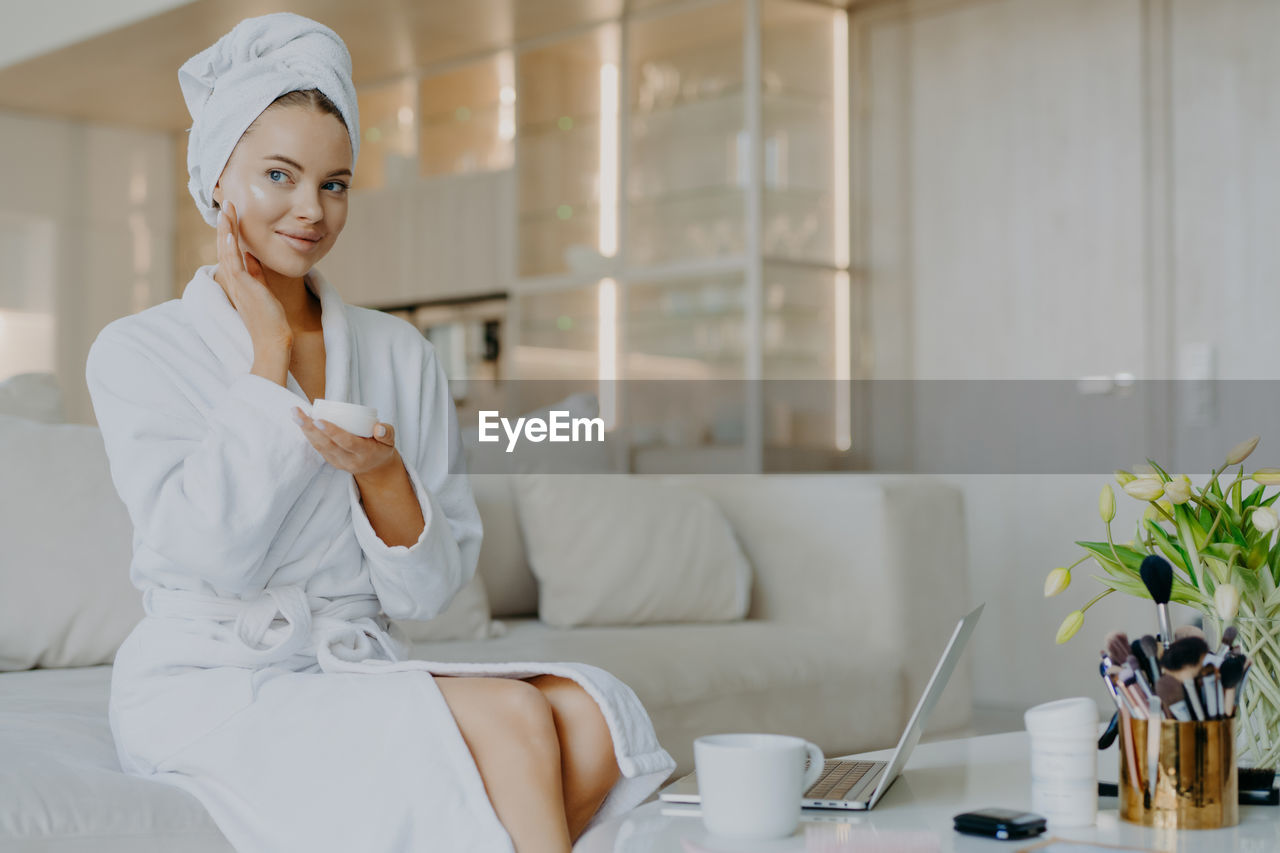 Young woman applying moisturizer while sitting on sofa at home