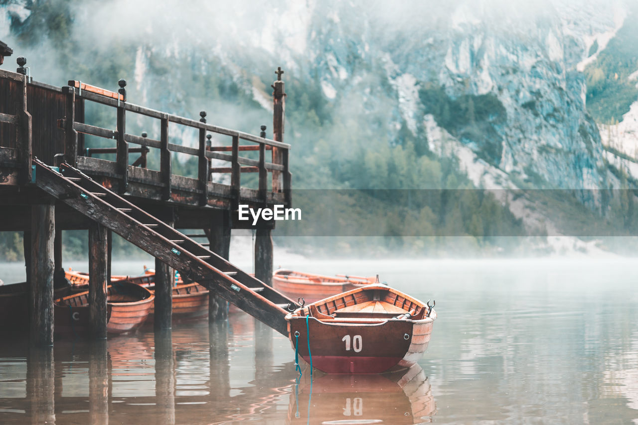 Boats Moored By Pier On Lake Against Mountains During Foggy Weather