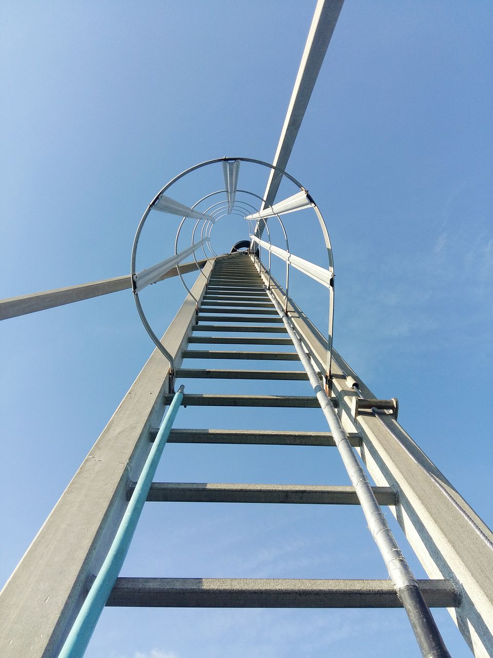 sky, low angle view, environmental conservation, alternative energy, renewable energy, fuel and power generation, wind turbine, wind power, turbine, clear sky, nature, day, architecture, blue, no people, environment, built structure, ladder, sunlight, metal, outdoors, directly below
