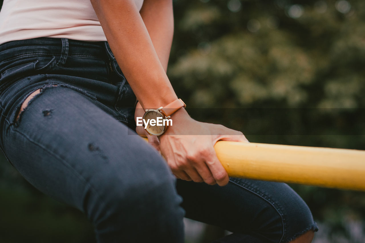 Midsection of woman holding hands sitting outdoors