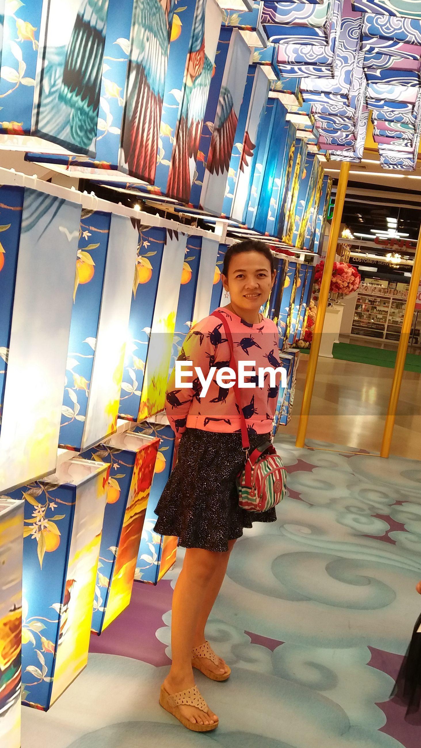 Full length of smiling girl standing indoors