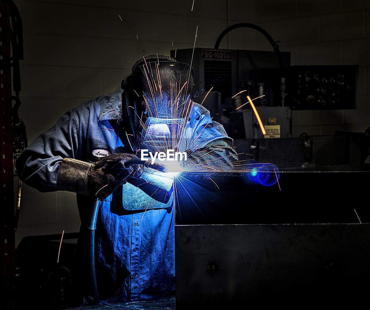 Welder welding metal in workshop